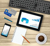 Business office workplace.Top view. Tablet with financial graph on screen,  coffee cup, smartphone, credit cards,notepad. Business office workplace.Top view Royalty Free Stock Image