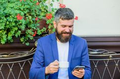 Business online sales. Manager always in touch. Man bearded businessman sit terrace with smartphone and cup of coffee. Take care of business even while enjoy stock images