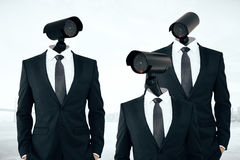 Business/organization security management. Three businessmen in suits with CCTV cameras instead of heads on abstract city background. Business/organization stock photography