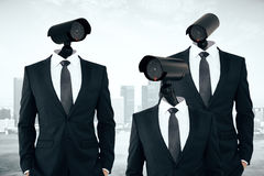 Business/organization security management. Three businesspeople in suits with CCTV cameras instead of heads on abstract city background. Business/organization Royalty Free Stock Photo
