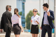 Business outdoor. Confident business people discussing project while standing in front of office Royalty Free Stock Images