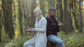 Business outdoor. Couple working - using laptop and smartphone outdoor. People in love on Autumn background. Autumn. Travels. Cheerful carefree autumn couple in stock video footage