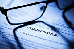 Business Overdue Account Bills. An overdue account with reading glasses Stock Photo