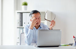 Tired businessman with glasses at laptop in office. Business, overwork, deadline and people concept - tired businessman with eyeglasses and laptop computer Royalty Free Stock Image