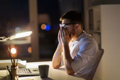 Tired businessman with laptop at night office. Business, overwork, deadline and people concept - tired man with laptop computer working at night office Royalty Free Stock Images