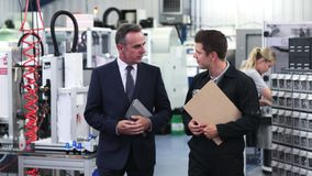 Business owner in factory shaking hands with engineer
