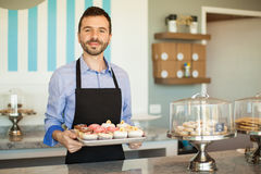 Business owner in his cake shop. Handsome young man showing a tray of cupcakes from his own cake shop royalty free stock image