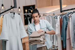 Business owner holding pile of pants while working in boutique before opening. Young business owner holding pile of pants while working in boutique before Royalty Free Stock Photo