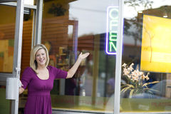 Business owner opening shop. A happy business owner opening her shop door Stock Photo