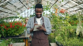 Business owner walking in greenhouse writing in notebook doing inventory smiling. Business owner African American man in apron is walking in greenhouse writing stock video footage