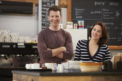 Business owners behind the counter at their cafe, close up Stock Photography