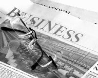 Business pages. A news paper garnished with a pair of reading glasses royalty free stock photography
