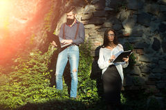 Business pair outdoor. Business young pair of slim women and men with long lush black beard with office devices of laptop glasses mobile phone paper folder royalty free stock photo