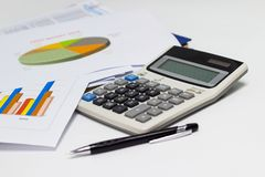 Business paper graphs and pen with charts report, calculator on desk of financial planning Royalty Free Stock Image