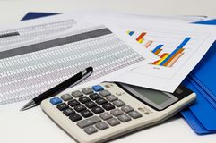 Business paper graphs and pen with charts report, calculator on desk Royalty Free Stock Image