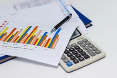 Business paper graphs and pen with charts report, calculator on desk of financial planning Stock Photos
