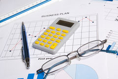 Business papers with graphs, charts, glasses, pen and calculator Stock Photos
