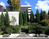 Business Park Benches. A pair of benches flank concrete steps that lead into a business park with lush landscaping and several modern buildings stock image