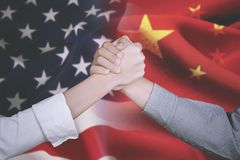 Business partner with America and China flag. Hands of young business partner shaking hands after deal business with America and China flag in the background stock image