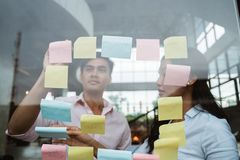 Business partner brainstorming by sticking idea into the glass window royalty free stock photos