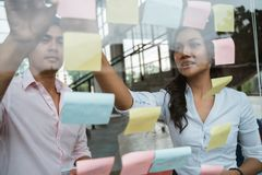 Business partner brainstorming by sticking idea into the glass window stock photo