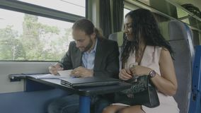 Business partner filling information and signing the contract agreement discussing with businesswoman during the professional trip. Young bearded business stock video