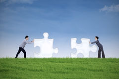 Business partner putting together two puzzle pieces Stock Photography