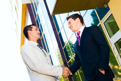 Business partner shaking hands. Two happy successful business partner shaking hands outdoor Stock Image