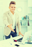 Business partner welcoming somebody. At desk in office Stock Images