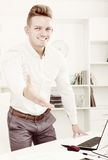 Business partner welcoming somebody. Smiling business partner welcoming somebody at desk in office Stock Photos