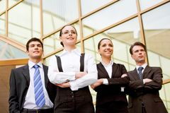 Business partners. Portrait of smart associates standing in row and looking forwards with successful woman in front Stock Photo