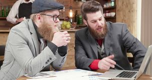 Business partners analyzing and comparing data from the computer. Handsome young man during a meeting in a small pub stock video
