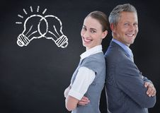 Business partners back to back with lightbulb doodles against navy chalkboard Stock Images