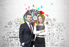 Business partners and business idea. Bearded businessman in a suit and a smiling businesswoman are standing near a concrete wall with a brain with gears and a Royalty Free Stock Photo