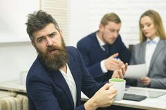 Business partners or businessman at meeting, office background. Negotiations concept. Man with beard drinks tea while. Waiting for bosses decision. Business Royalty Free Stock Photography
