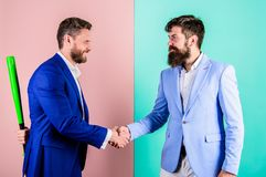Business partners competitors office colleagues shaking hands. Tricky first impression. Do not trust him. Hidden danger. Businessman hides bat behind back royalty free stock images