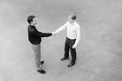 A business partners concluded a bargain on the street. Black and white image of the business partners concluding a bargain. Focus is made on top of the gray Royalty Free Stock Photography