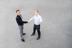 A business partners concluded a bargain on the street. Image of the business partners concluding a bargain. Focus is made on top of the gray background of the Stock Photo