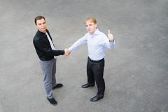 A business partners concluded a bargain on the street. Image of the business partners concluding a bargain. Focus is made on top of the gray background of the Stock Image