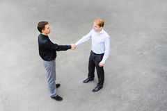 A business partners concluded a bargain on the street. The image of the business partners concluding a bargain. Focus is made on top of the gray background of Royalty Free Stock Images