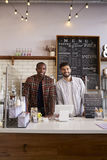 Business partners at the counter of a coffee shop, vertical royalty free stock images