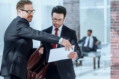 Business partners discuss the document standing in the office lobby. The concept of business relationship royalty free stock photo