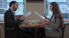 Business partners discuss documents during lunch at cafe. Business partners discuss documents, diagrams, statistics during lunch at restaurant stock video footage