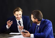 Business partners discuss project. Investment strategy, business growth. Busy people with cheerful faces, documents, smartphone. Friends think about Royalty Free Stock Image