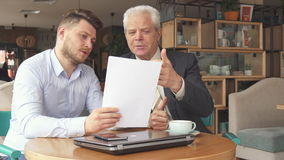 Business partners discuss some papers. Two male business partners discussing some papers at the cafe. Young bearded man turning pages of some document. Senior stock video