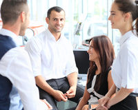 Business partners discussing documents and ideas at meeting Stock Images