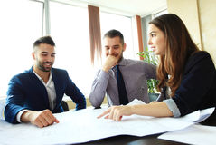 Business partners discussing documents and ideas at meeting Royalty Free Stock Image