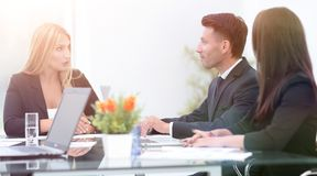 Business partners discussing a financial transaction. Sitting at your Desk Stock Images