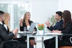 Business partners discussing a financial transaction. Sitting at your Desk Stock Photo