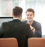 Business partners discussing in meeting hall with their collegue Stock Photo